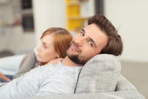 Man looking at camera with woman at side on a couch