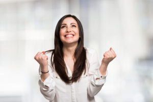 woman smiling and holding her fists up