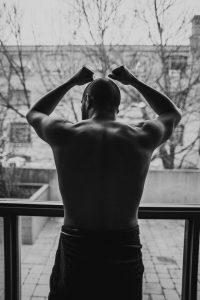 man in a towel facing window
